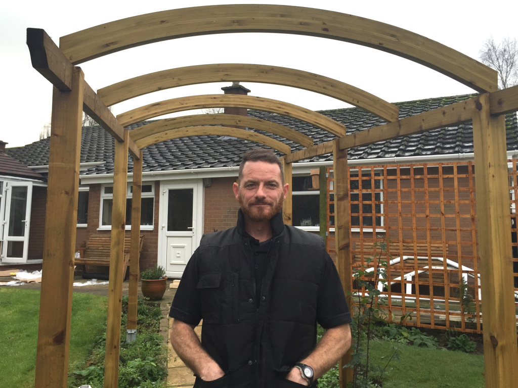 Russell stands with a pergola completed for a client.