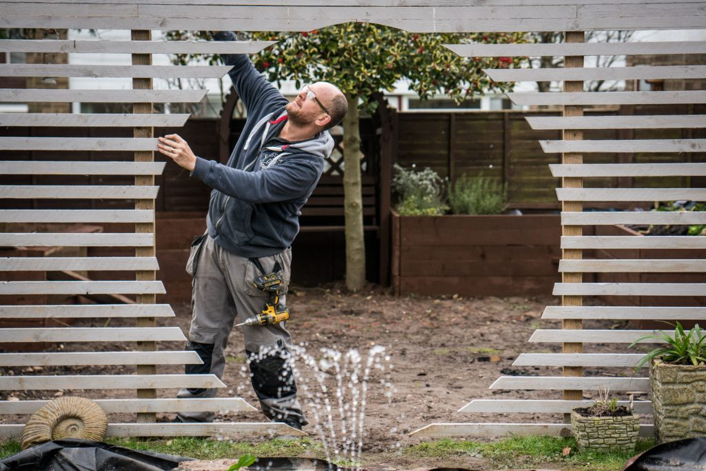 Handyman Ian Nicholson puts the finishing touches to a dramatic moon gate in a Worthing garden.